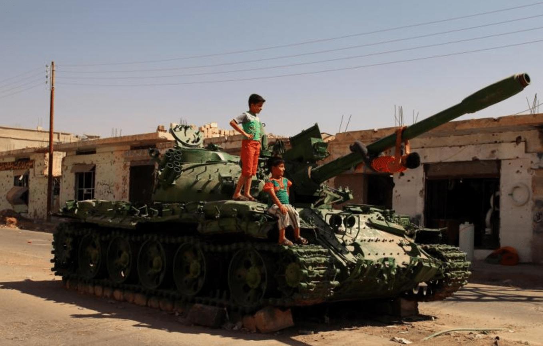 Alcuni bambini giocano su un carro armato danneggiato nella città di Bosra al-Sham, nel governatorato di Deraa, in Siria