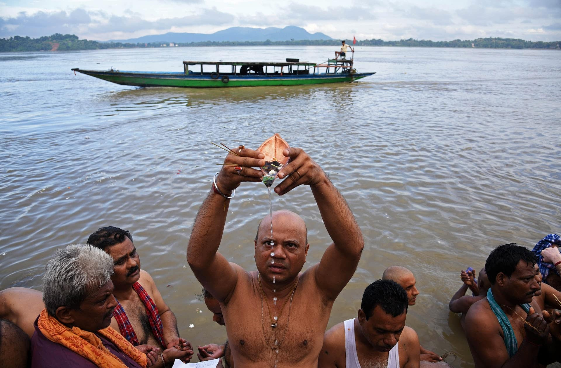 Alcuni devoti induisti durante la cerimonia di Tarpana, un rito religioso tenuto sul fiume Brahmaputra, a Guwahati, in India, in onore delle anime dei cari defunti