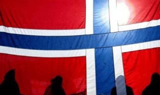 Alcune persone a Oslo, dietro una bandiera della Norvegia