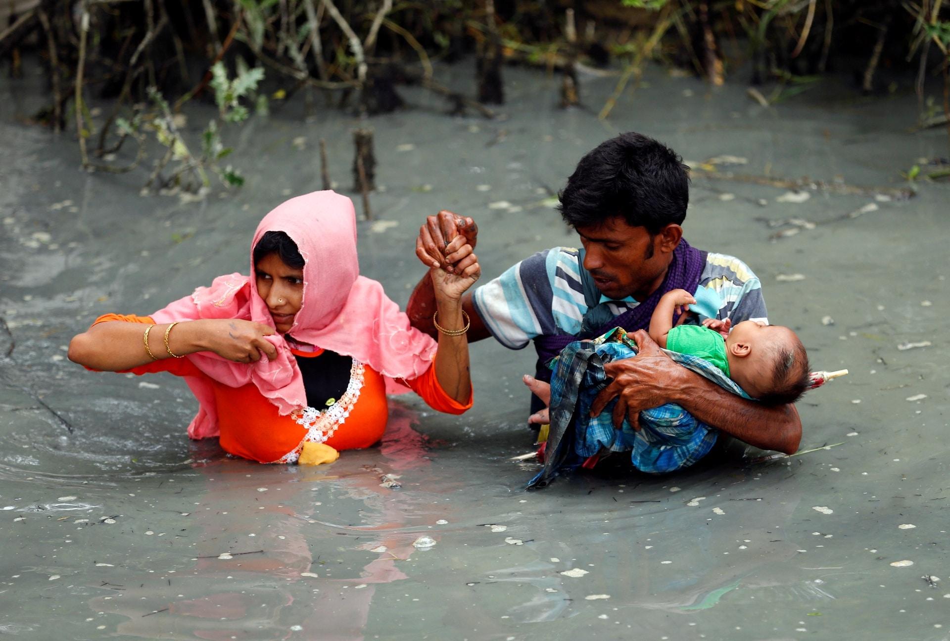 Una coppia di rifugiati rohingya attraversa il fiume Naf, in Bagladesh per fuggire dalle persecuzioni dei militari birmani.