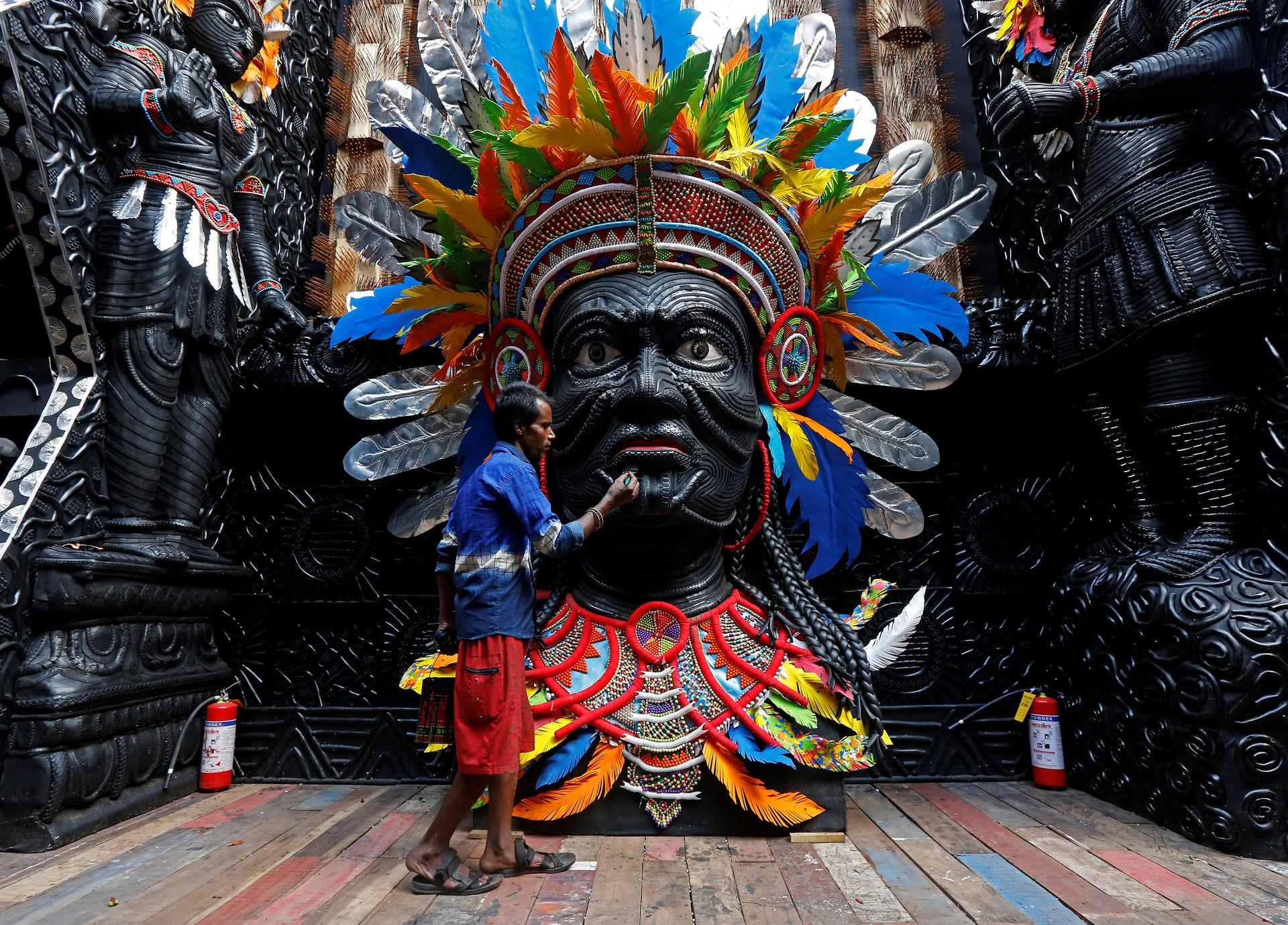 Un artista al lavoro su una statua che rappresenta la dea indù Durga, prima del festival religioso Durga Puja a Calcutta, in India