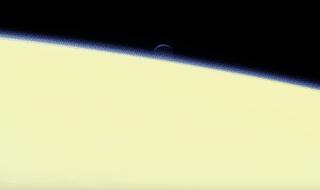 Una delle ultime immagini inviate a Terra dalla sonda Cassini mostra la luna di Saturno Encelado sullo sfondo dell'atmosfera del pianeta gassoso