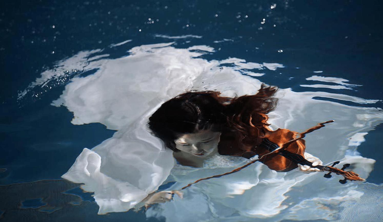 Una sposa cinese si lascia fotografare sott'acqua mentre finge di suonare un violino